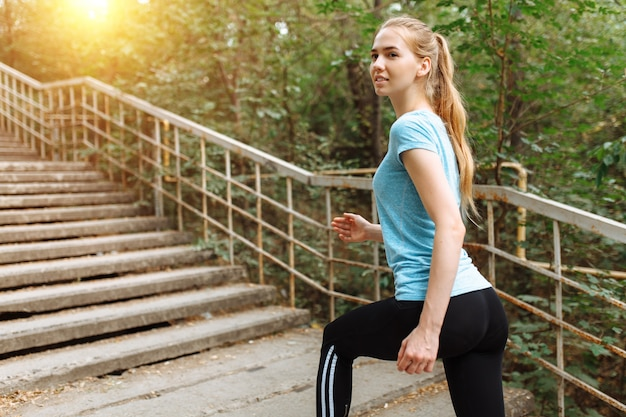 Beautiful young woman jogging on the steps