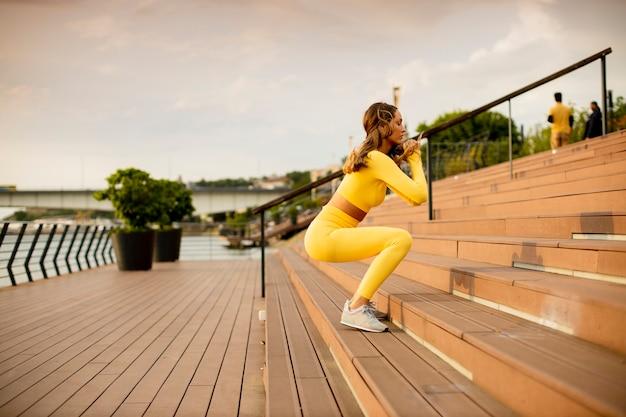 Красивая молодая женщина прыгает по лестнице на берегу реки