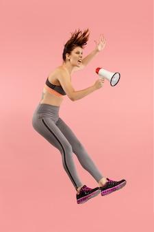 Красивая молодая женщина прыгает с мегафоном, изолированным на красном фоне. девушка runnin в движении или движении. концепция человеческих эмоций и мимики