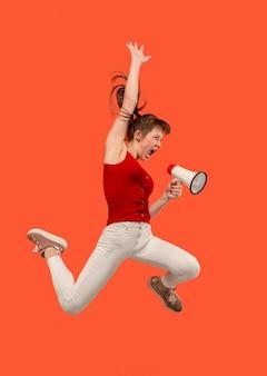 빨간색 배경 위에 절연 확성기와 점프하는 아름 다운 젊은 여자. 모션 또는 움직임에서 runnin 소녀. 인간의 감정과 표정 개념