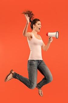 赤い背景の上に分離されたメガホンでジャンプする美しい若い女性。動いているまたは動いているrunninの女の子