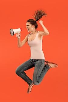赤い背景の上に分離されたメガホンでジャンプする美しい若い女性。動きや動きで走っている女の子。