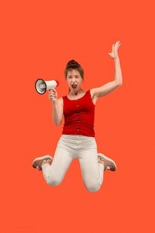 赤い背景の上に分離されたメガホンでジャンプする美しい若い女性