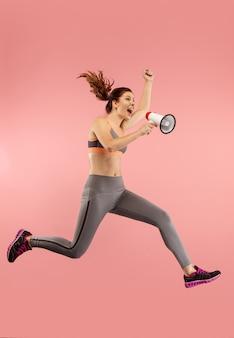 빨간색 배경 위에 절연 확성기와 점프하는 아름 다운 젊은 여자