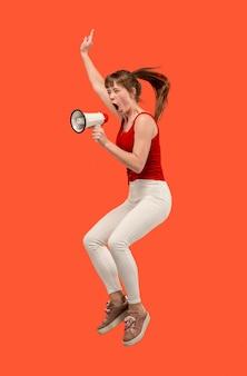 Bella giovane donna che salta con il megafono isolato su sfondo rosso. ragazza che corre in movimento o in movimento. le emozioni umane e il concetto di espressioni facciali