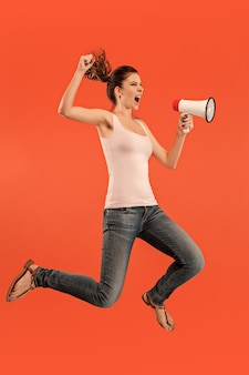 Beautiful young woman jumping with megaphone isolated over red background. running girl in motion or movement.