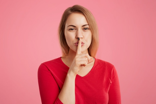 Beautiful young woman keeps fore finger on lips, shows silence sign, tries to keep personal information in secret