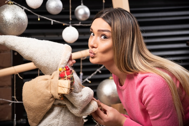 Beautiful young woman kissing doll at home.
