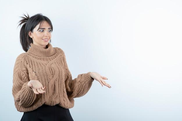 Bella giovane donna in maglione lavorato a maglia in piedi e in posa sul muro bianco