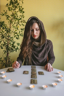 Beautiful young woman lays out cards on the table with candle lights