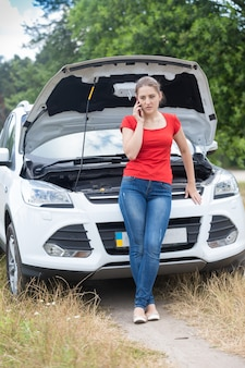 Beautiful young woman leaning on broken car and calling auto service
