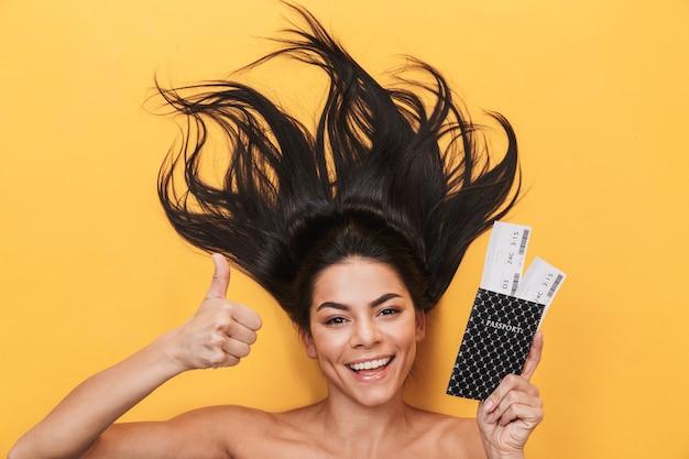 아름다운 젊은 여성은 티켓이 있는 여권을 들고 노란 벽에 고립되어 엄지손가락을 치켜든다