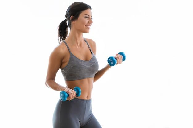 Beautiful young woman lifting dumbbells at home.
