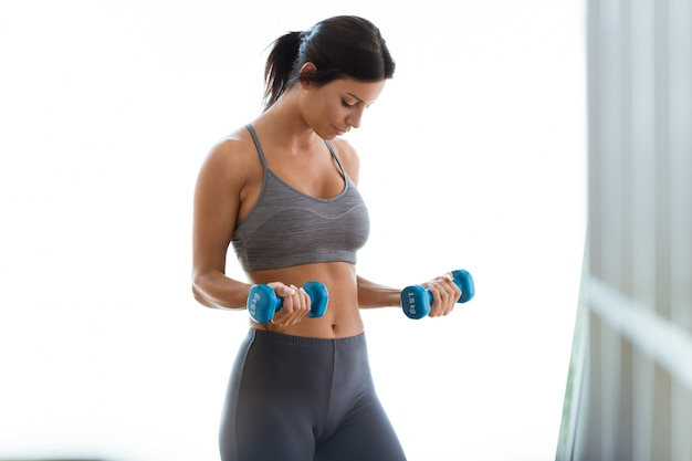 Beautiful young woman lifting dumbbells at home.