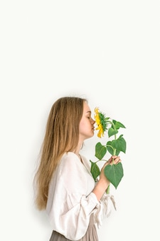 Beautiful young woman in linen dress holding sunflower on white