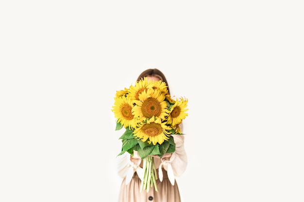 Beautiful young woman in linen dress holding sunflowers bouquet on white