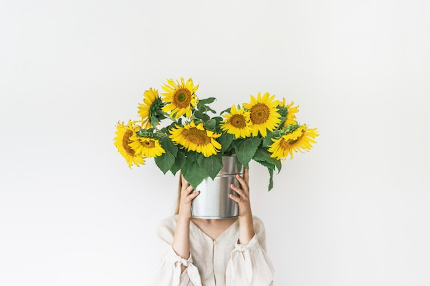 Beautiful young woman in linen dress holds sunflowers bouquet in a tin bucket on white.