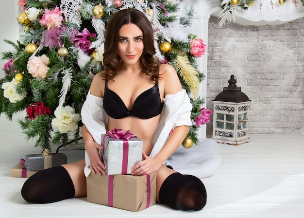 Beautiful young woman in lingerie with gift boxes