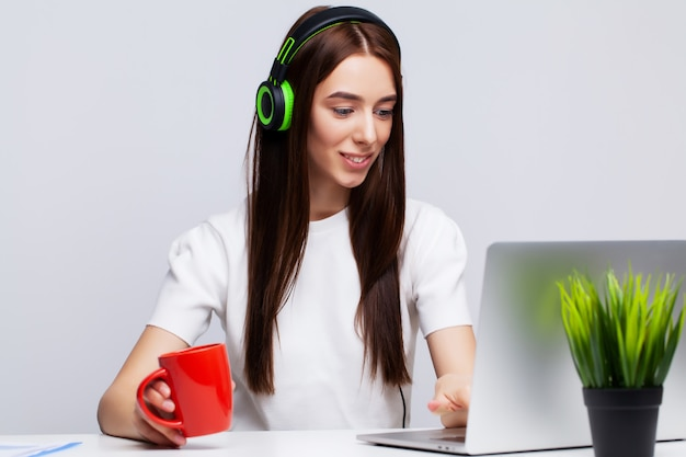 Beautiful young woman listening to music in headphones working on laptop in the office