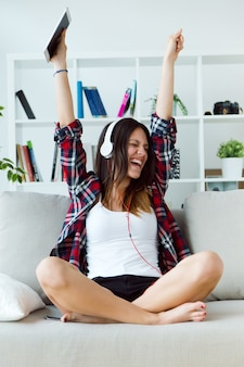 Beautiful young woman listening to music at home.