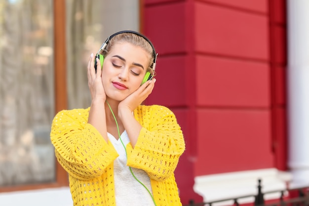 Beautiful young woman listening to music outdoors