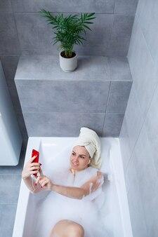 Красивая молодая женщина, слушать музыку и петь, принимая ванну дома. расслабьтесь после тяжелого дня. расслабляющая спа-процедура.