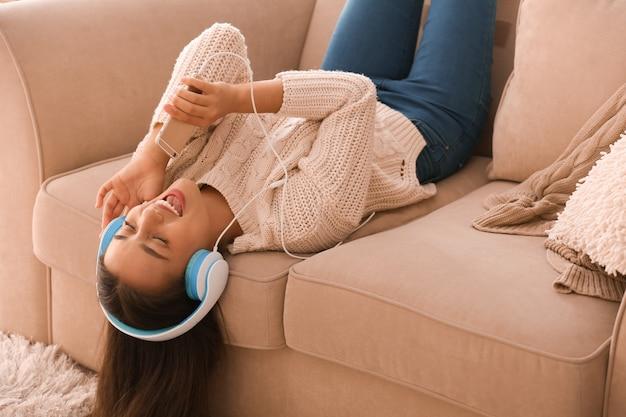Красивая молодая женщина, слушающая музыку дома