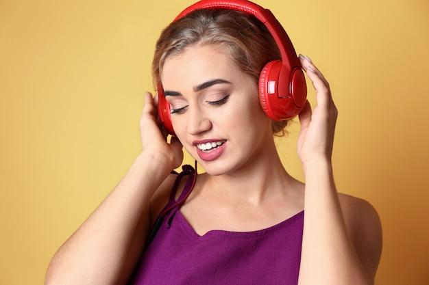 Красивая молодая женщина, слушающая музыку на цветном фоне