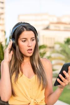 屋外で音楽を聴く美しい若い女性
