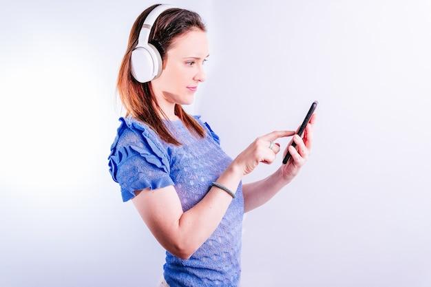 흰색 바탕에 헤드폰과 스마트폰으로 음악을 듣고 있는 아름다운 젊은 여성