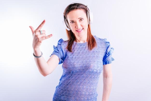 헤드폰을 끼고 음악을 들으며 손으로 헤비메탈 사인을 하는 아름다운 젊은 여성