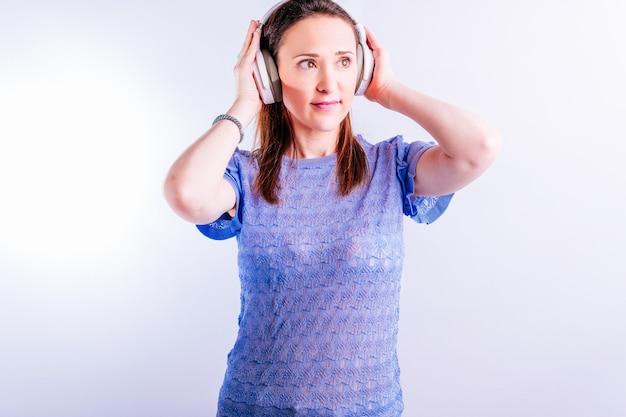 흰색 바탕에 헤드폰을 끼고 음악을 듣고 있는 아름다운 젊은 여성
