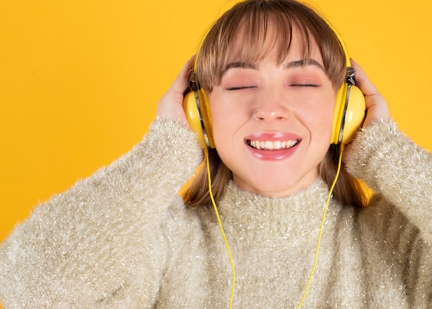 A beautiful young woman listens to music with headphones with closed eyes, yellow background