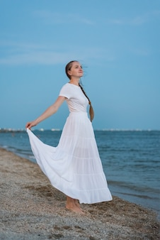 Beautiful young woman in long white dress standing on sandy beach on sea