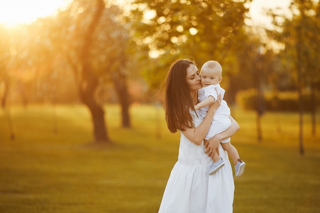 Beautiful young woman in a long white dress with a cute little baby boy in shirt and shorts on her hands posing at the green garden in sunny summer day