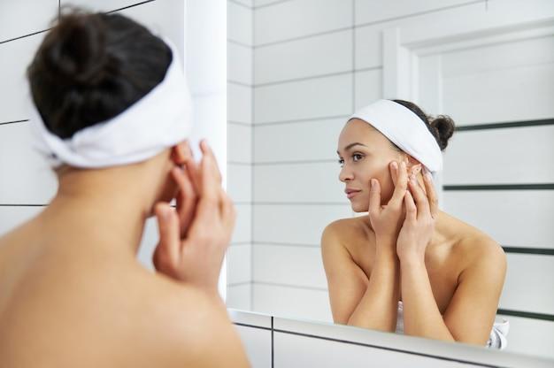 美しい若い女性が鏡マッサージの顔を見て