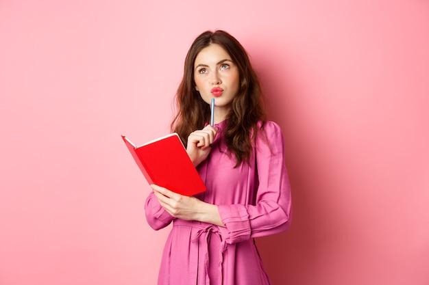 아름 다운 젊은 여자 사려 깊은 모습, 노트북에 쓰기, 플래너 또는 일기를 들고, 분홍색 벽에 서있는 그녀의 일정을 계획합니다.