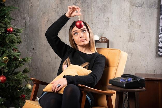 クリスマスツリーの横にあるボールを見ている美しい若い女性。