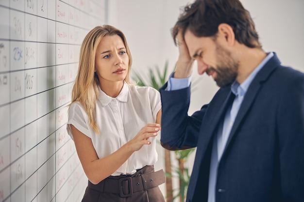 Красивая молодая женщина, глядя на коллегу с обеспокоенным выражением лица, в то время как мужчина страдает головной болью