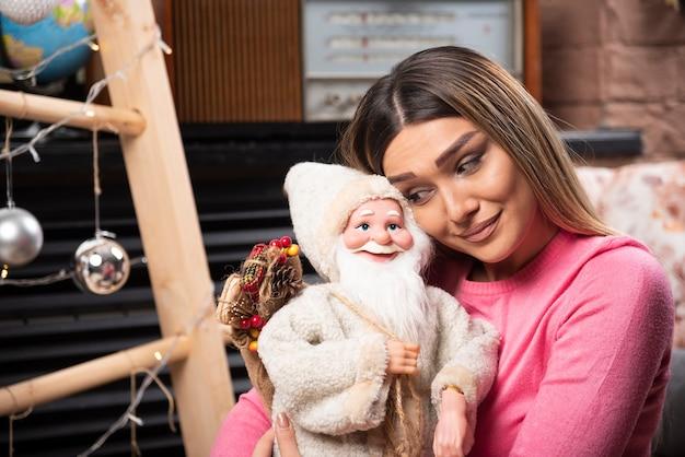 家で人形を見ている美しい若い女性。