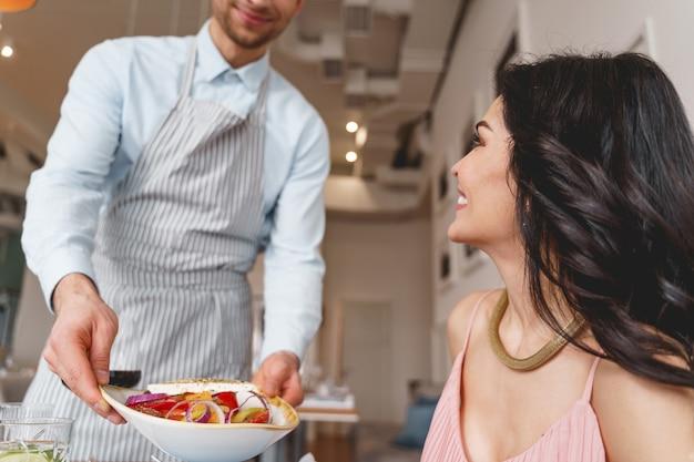 男性のカフェワーカーを見て、おいしいサラダのプレートを持って笑っている美しい若い女性