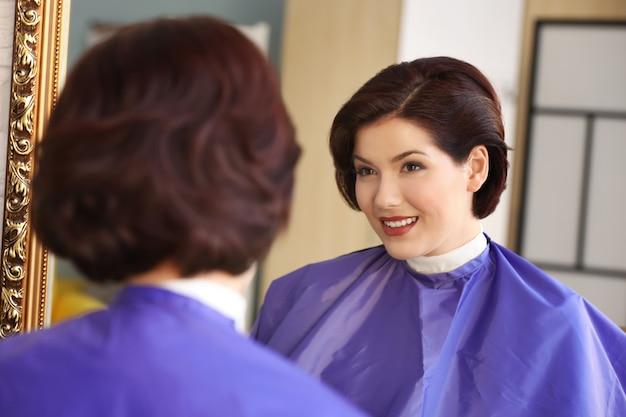Красивая молодая женщина, глядя в зеркало в салоне