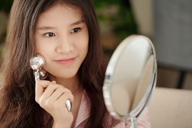 美容液を塗った後、ローラーで顔をマッサージするときに鏡を見ている美しい若い女性