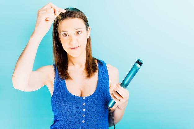 Красивая молодая женщина, глядя на кончики ее волос, держа выпрямители для волос на синем фоне