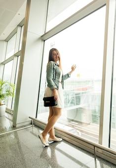 Красивая молодая женщина, глядя в окно в современном терминале аэропорта