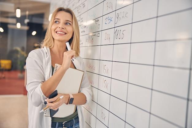 Красивая молодая женщина смотрит в сторону и улыбается, держа маркер, смартфон и альбом для рисования