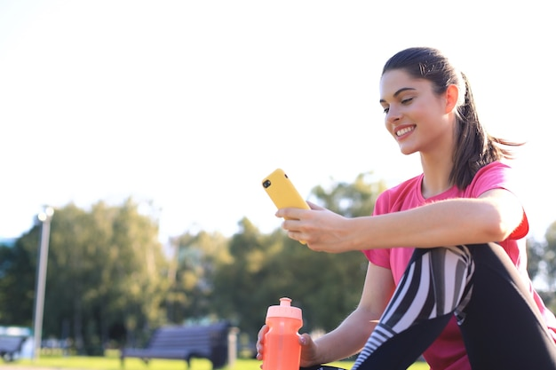 Beautiful young woman looking away while sitting on exercise mat at park, relaxing after training and using smartphone.