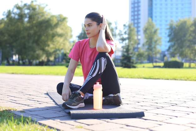 Beautiful young woman looking away while sitting on exercise mat at park, relaxing after training.