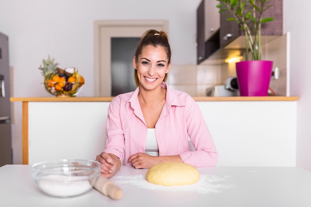 Beautiful young woman looking at camera and smiling while baking in kitchen at home. smiling young housewife making dough