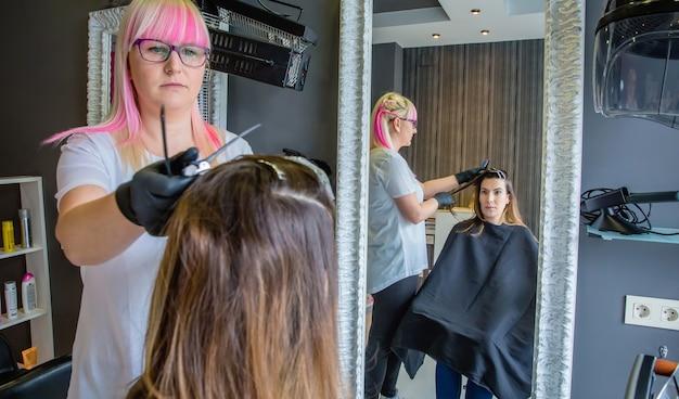 머리 색깔이 바뀌는 과정에서 머리를 빗고 있는 미용사에게 거울을 보고 있는 아름다운 젊은 여성